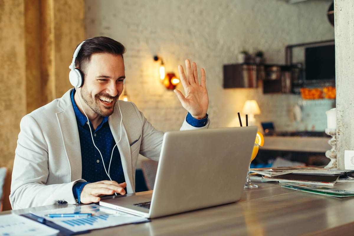 A man is leaning English online via video conference an is waving at his teacher.