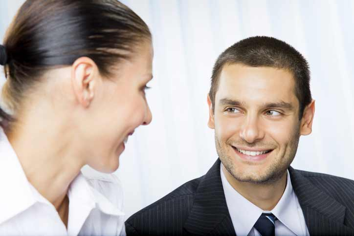 French course one-to-one. Teacher and participant in business dresses are smiling at each other.
