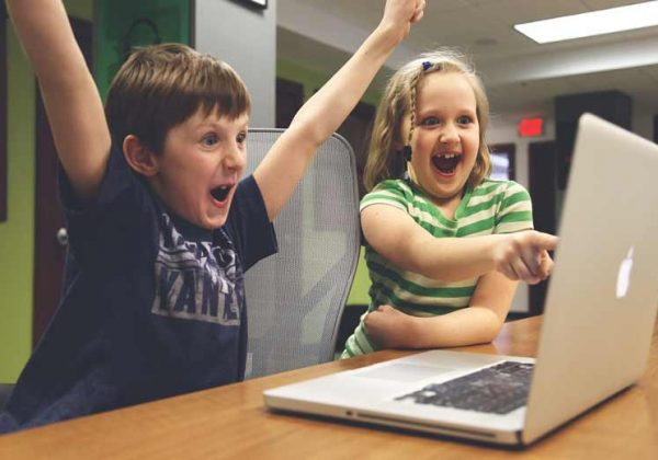 Two kids are learning German online and are sitting in front of a computer, cheering. Photographer > getty images