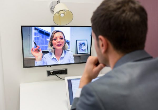A young man is learning Russian online in a video conference. The teacher is explaining and is raising her hand - Photographer > getty images