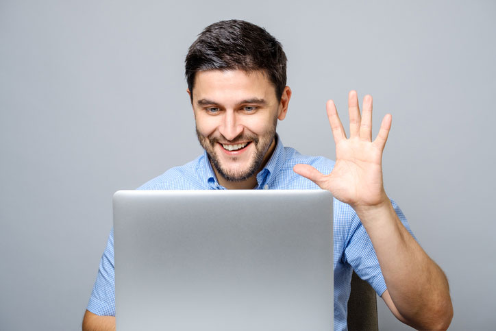 A young man is learning Spanish online via video conference and is waving at his teacher.